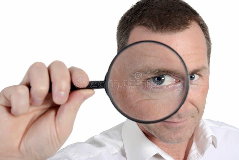 Hombre con la lupa foto de archivo