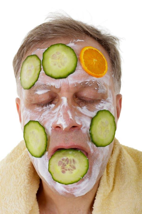 Hombre con la máscara facial del pepino y de la naranja fotografía de archivo