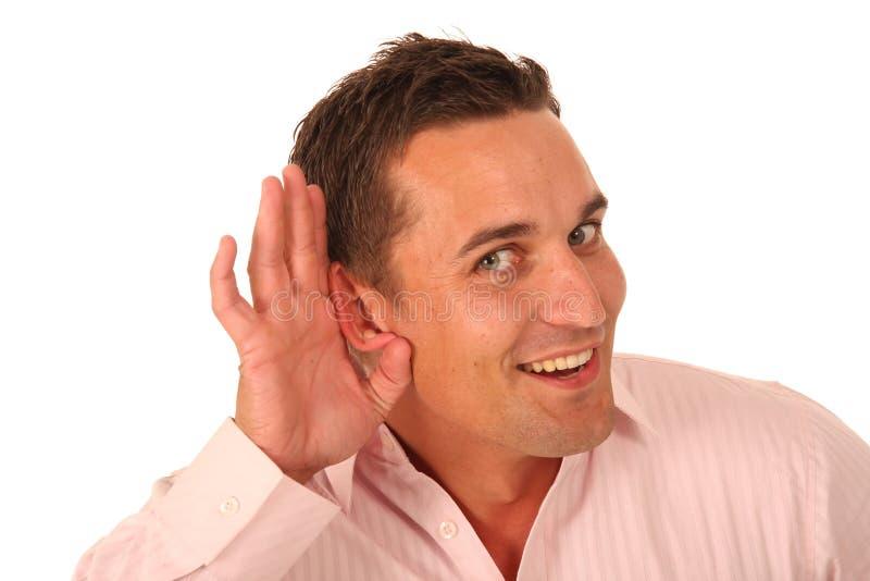 Hombre con la mano ahuecada al oído imagen de archivo libre de regalías