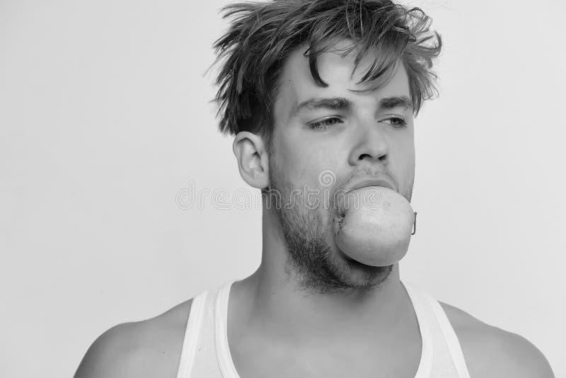 Hombre con la manzana verde en su boca Individuo con la cara ocupada aislada en fondo gris claro foto de archivo