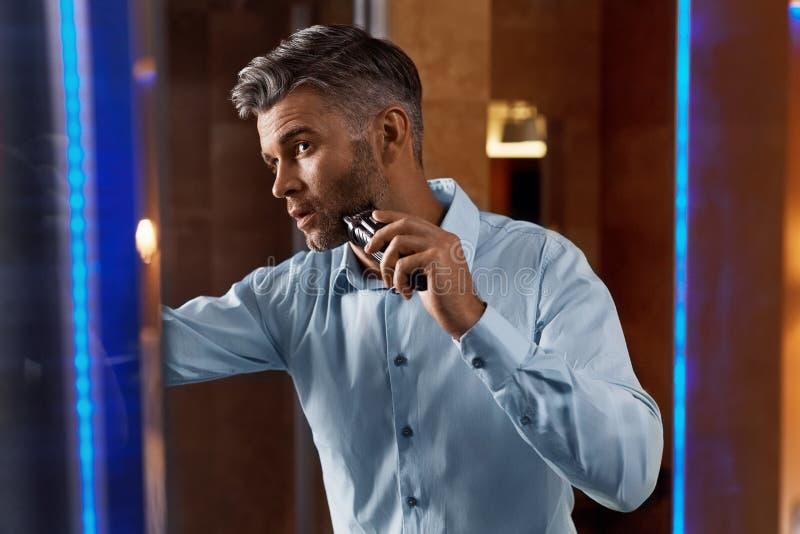 Hombre con la maquinilla de afeitar eléctrica que afeita la cara en cuarto de baño Preparación de los hombres fotografía de archivo libre de regalías