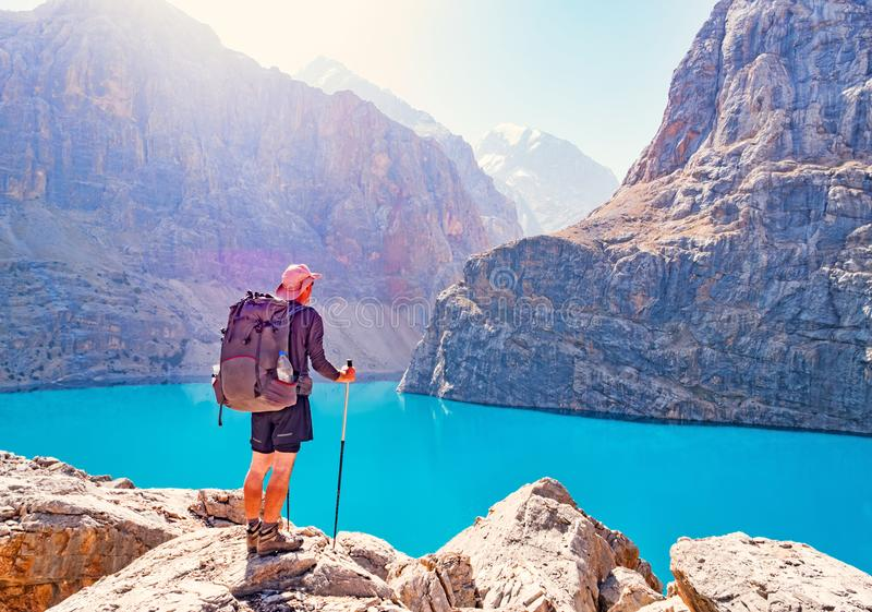 Hombre con la mochila cerca del lago Alo grande en fondo de la montaña rocosa Fann Mountains foto de archivo