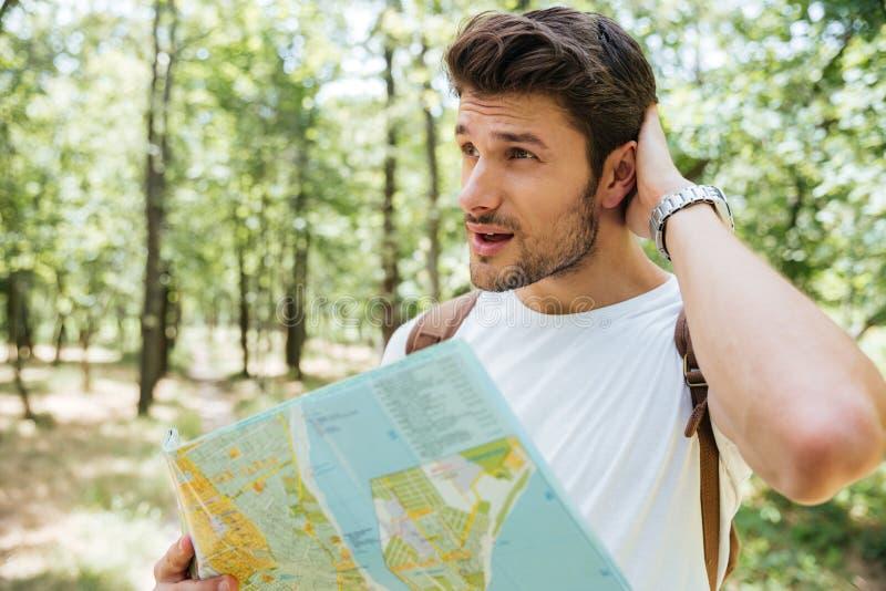 Hombre con la mochila que se coloca en bosque y que usa el mapa imagenes de archivo