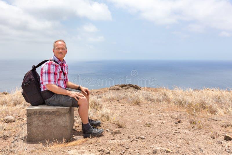 Hombre con la mochila que se sienta cuesta arriba en la costa de mar imagenes de archivo