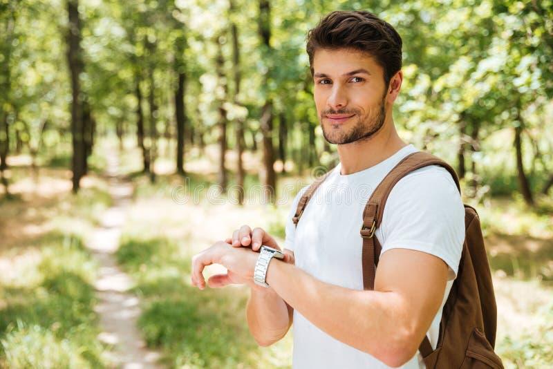 Hombre con la mochila y el reloj que se colocan en bosque imagen de archivo