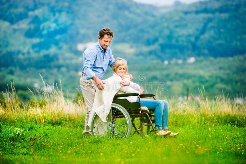 Hombre con la mujer en silla de ruedas imagenes de archivo