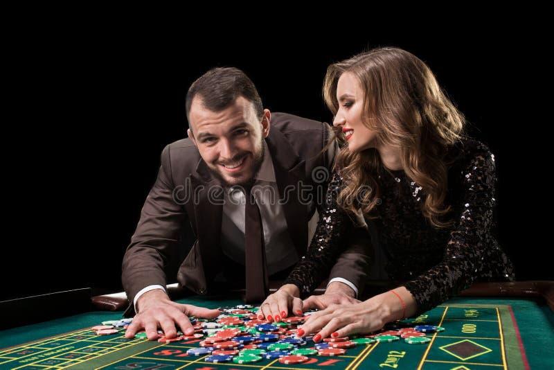 Hombre con la mujer que juega la ruleta en el casino Apego a imágenes de archivo libres de regalías