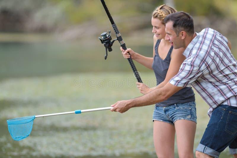 Hombre con la novia de la demostración de la caña de pescar cómo pescar imagen de archivo libre de regalías
