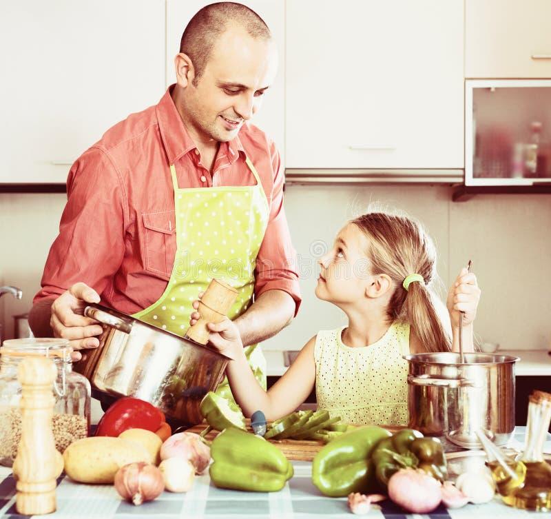 Hombre con la pequeña hija en la cocina imágenes de archivo libres de regalías