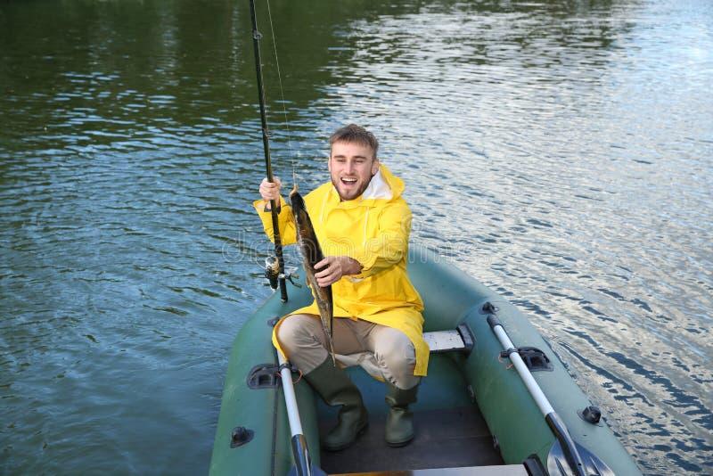 Hombre con la pesca de la barra del barco foto de archivo