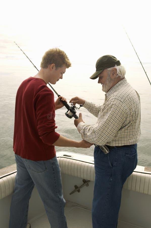 Hombre con la pesca del nieto en el yate fotos de archivo