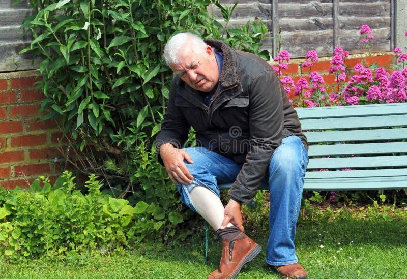 Hombre con la pierna dolorosa foto de archivo libre de regalías