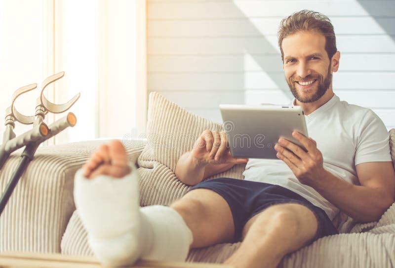 Hombre con la pierna quebrada imagen de archivo