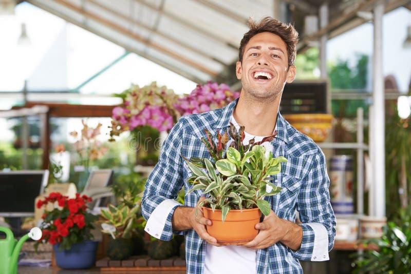 Hombre con la planta en centro de jardinería fotografía de archivo