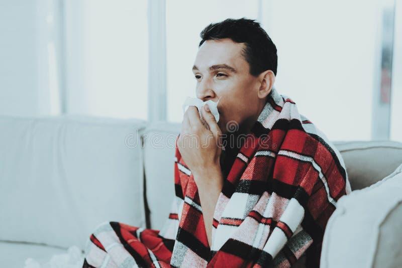 Hombre con la sentada fría en el sofá en manta a cuadros Hombre en el país Hombre joven enfermo Sofá blanco en sitio Individuo in imagenes de archivo