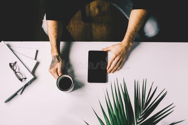 Hombre con la tableta de la tenencia del tatuaje en la tabla del escritorio de oficina con, fuentes, la flor y la taza de café Vi fotografía de archivo