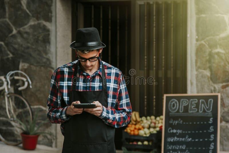 Hombre con la tableta en frente de la tienda foto de archivo libre de regalías