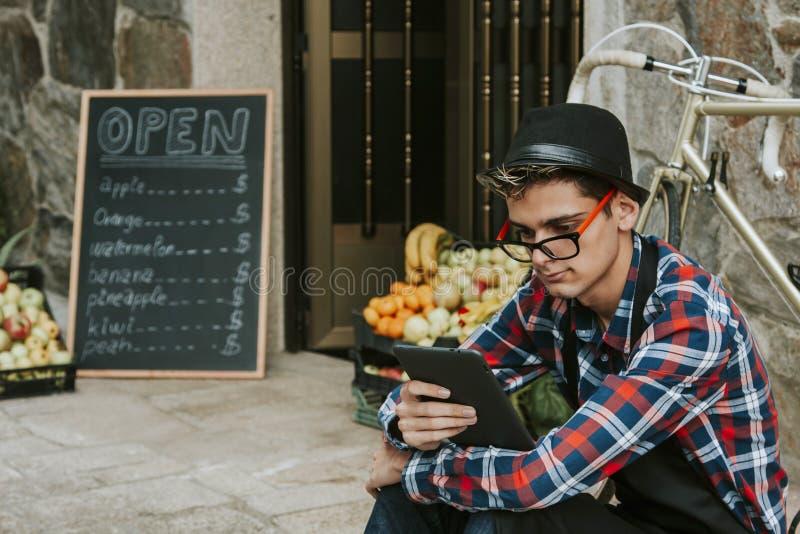 Hombre con la tableta en frente de la tienda imagen de archivo libre de regalías