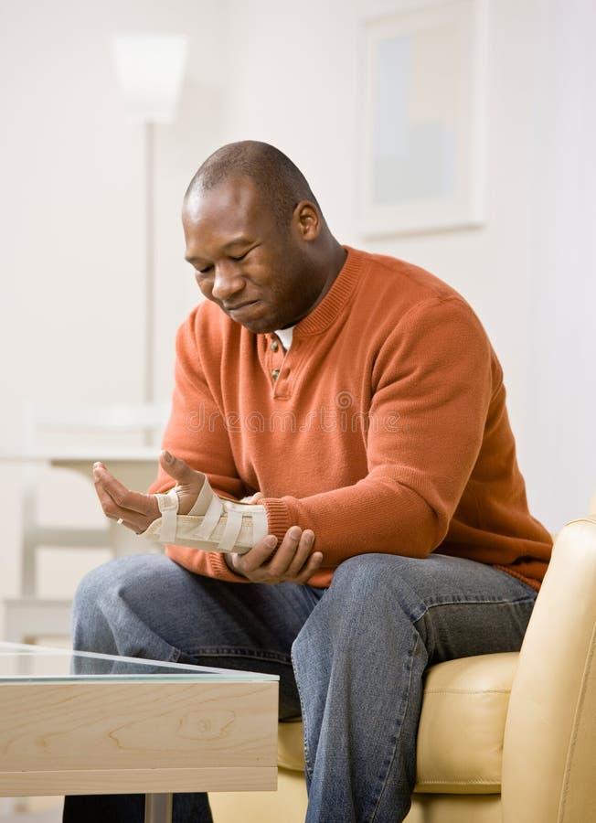 Hombre con la tablilla en dolor de lesión a su muñeca imagen de archivo