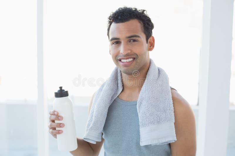 Hombre con la toalla alrededor del cuello que sostiene la botella de agua en estudio de la aptitud imágenes de archivo libres de regalías