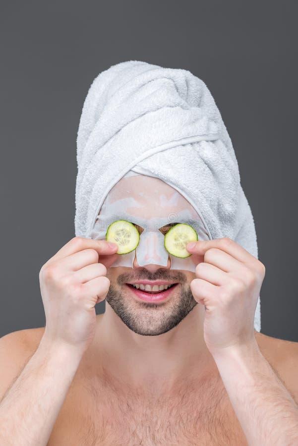 hombre con la toalla, la máscara del colágeno y las rebanadas del pepino en ojos, fotografía de archivo libre de regalías