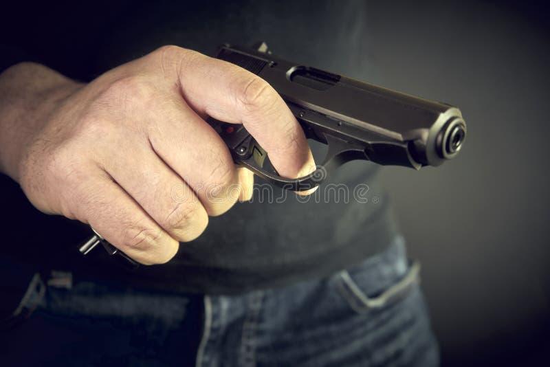 Hombre con la violencia de goma del ataque de la pistola del arma de la mano fotografía de archivo libre de regalías