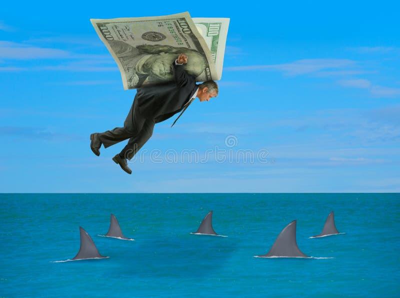 Hombre con las alas hechas del dinero que vuela sobre la escuela de tiburones foto de archivo libre de regalías