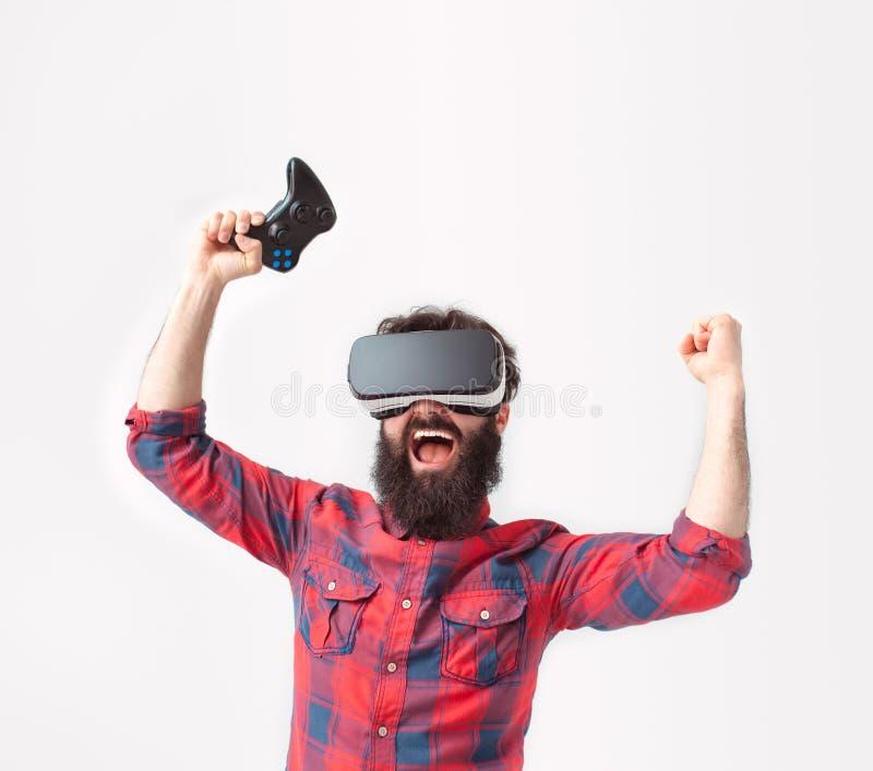 Hombre con las auriculares y el gamepad de VR imagenes de archivo