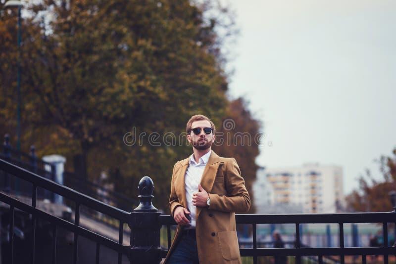 Hombre con las cerdas en una capa del otoño fotos de archivo