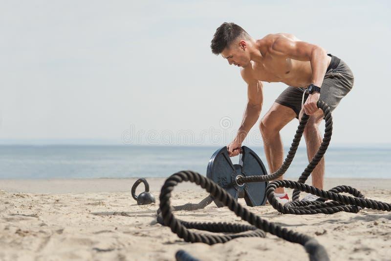 Hombre con las cuerdas en una playa en un día soleado imagen de archivo