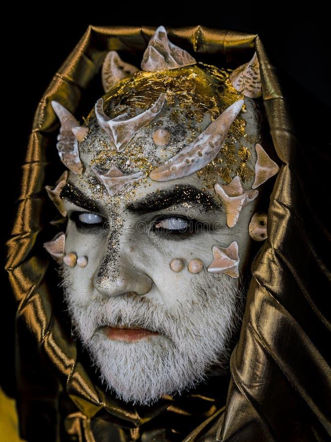 Hombre con las espinas o las verrugas, cara cubierta con brillos El hombre mayor con la barba blanca se vistió como monstruo Extr fotos de archivo