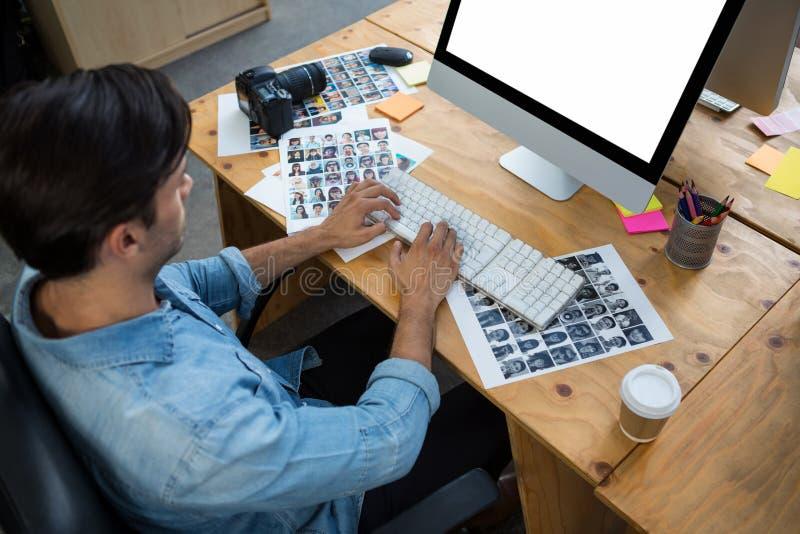Hombre con las fotografías que trabajan en PC de sobremesa foto de archivo libre de regalías