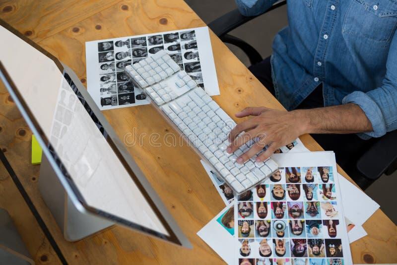 Hombre con las fotografías que trabajan en PC de sobremesa imagenes de archivo