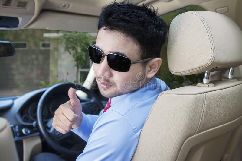Hombre con las gafas de sol en el asiento de conducción Mirada detrás y mostrar del pulgar para arriba fotos de archivo libres de regalías