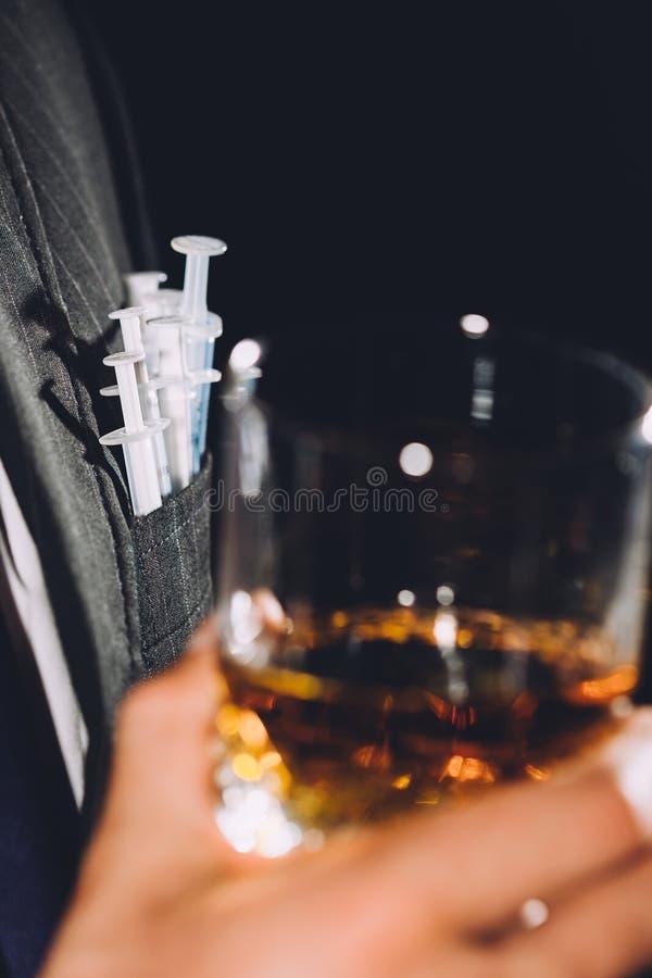 Hombre con las jeringuillas del alcohol y de las drogas foto de archivo libre de regalías