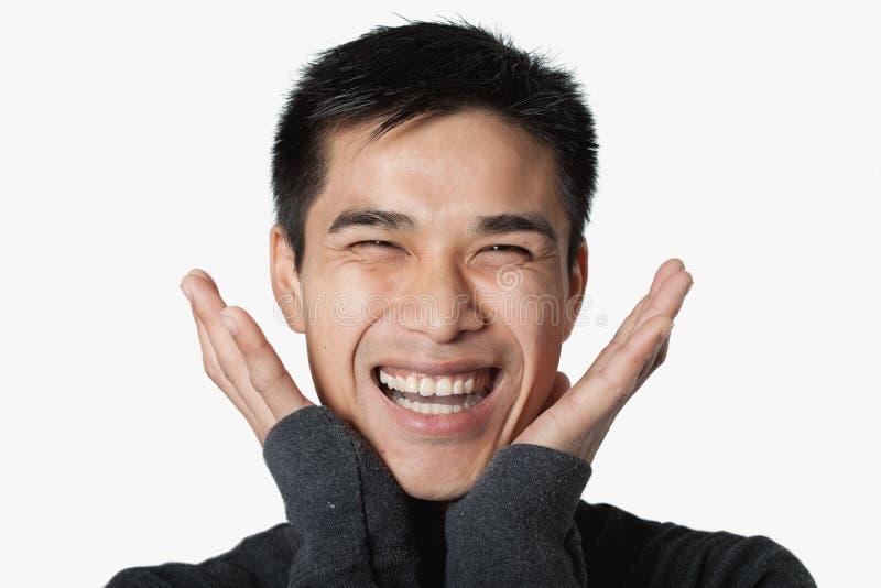 Hombre con las manos hasta su cara con sonrisa grande imagenes de archivo