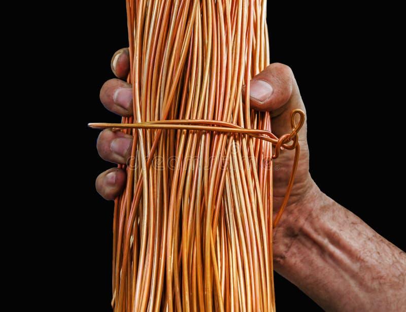 Hombre con las manos sucias que llevan a cabo un rollo del alambre de cobre aislado en negro fotos de archivo