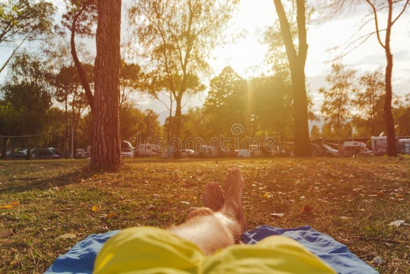 Hombre con las piernas cruzadas que se relajan en el prado que mira acampar y la puesta del sol imagen de archivo