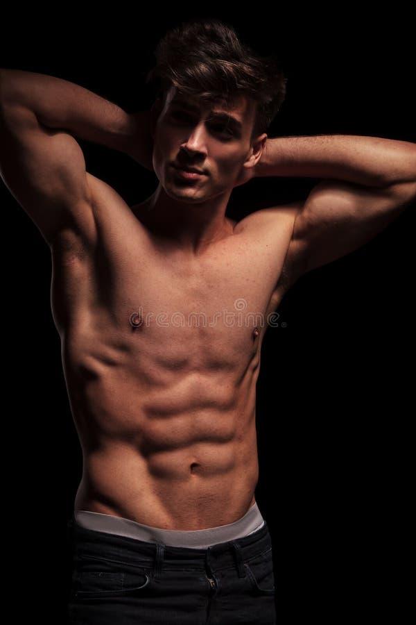 Hombre con las tetas al aire muscular que dobla sus brazos foto de archivo libre de regalías