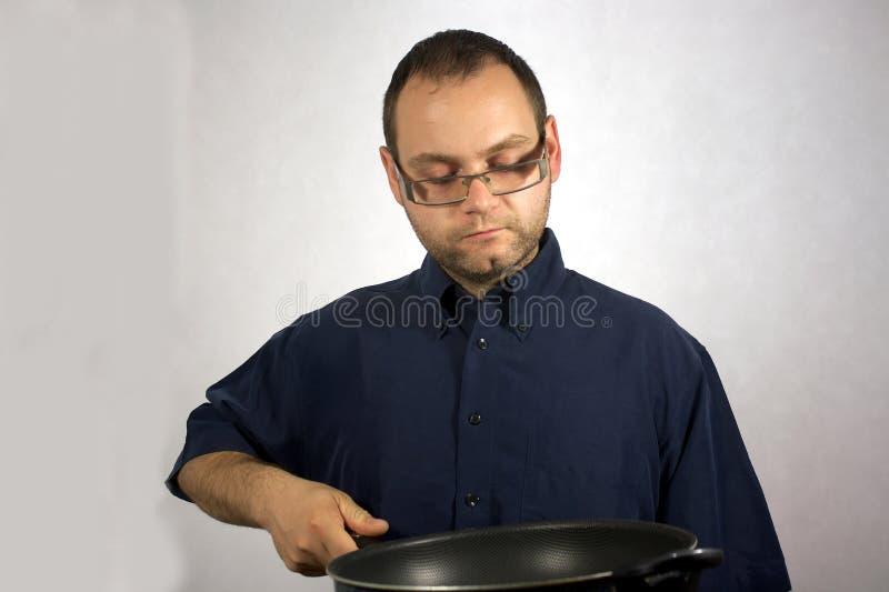 Hombre con los accesorios de la cocina foto de archivo libre de regalías