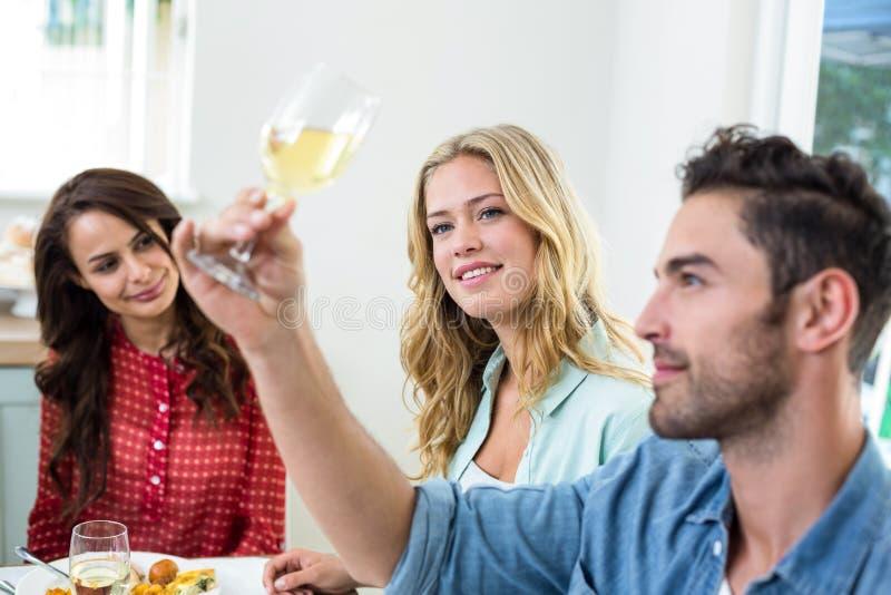 Hombre con los amigos que miran la copa de vino blanca imagenes de archivo