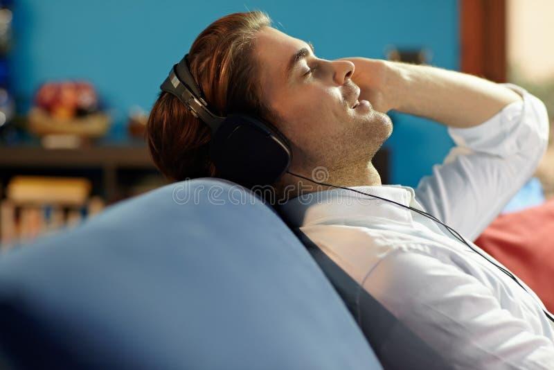 Hombre con los auriculares que escucha la música fotos de archivo