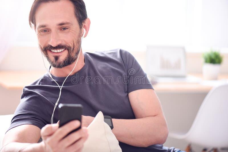 Hombre con los auriculares que miran el teléfono foto de archivo