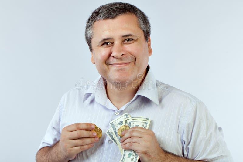 Hombre con los bitcoins y los dólares imagenes de archivo