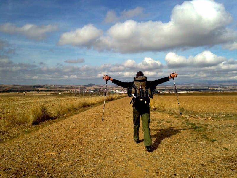 Hombre con los brazos de extensión de la mochila y el caminar en campo Concepto de Camino de Santiago Concepto del peregrinaje imagen de archivo libre de regalías