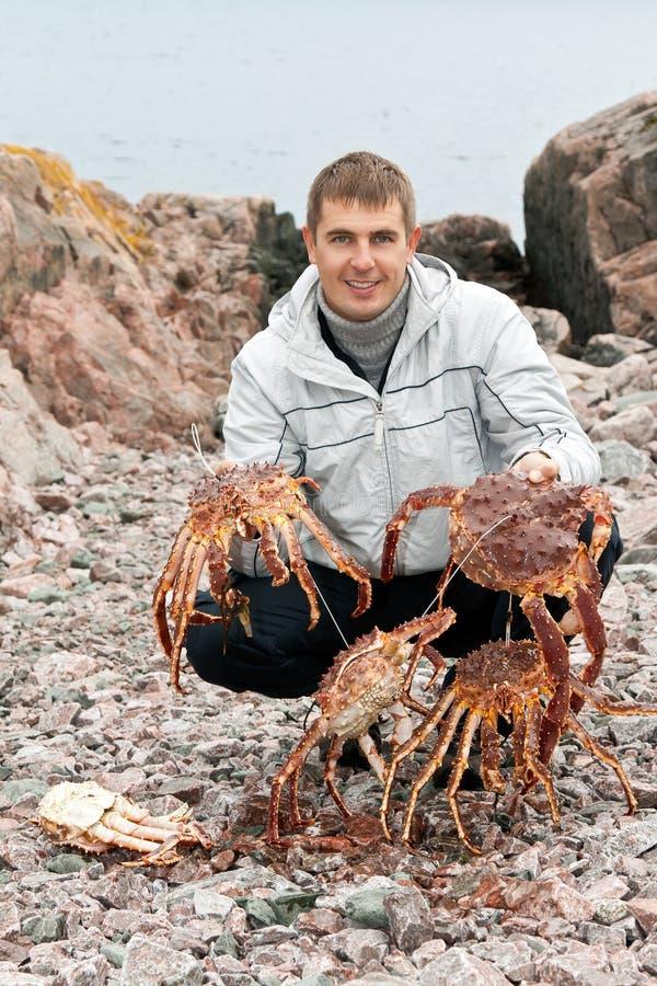 Hombre con los cangrejos en la costa de mar de Barents foto de archivo