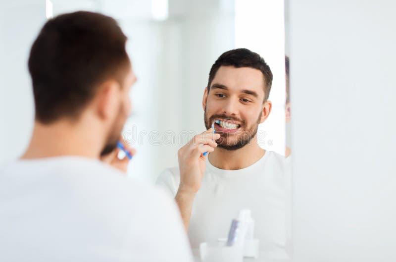 Hombre con los dientes de la limpieza del cepillo de dientes en el cuarto de baño imágenes de archivo libres de regalías