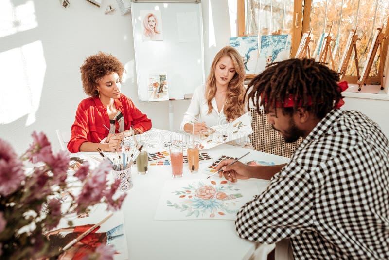 Hombre con los dreadlocks que se unen a sus amigos femeninos que dibujan imágenes foto de archivo libre de regalías