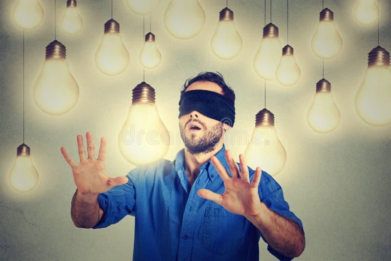 Hombre con los ojos vendados que camina a través de las bombillas que buscan para la idea brillante foto de archivo libre de regalías