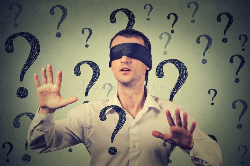 Hombre con los ojos vendados que estira sus brazos que salen a través de muchos signos de interrogación foto de archivo